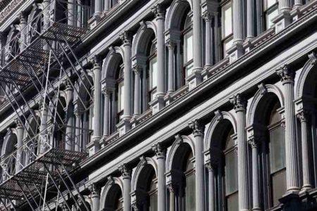 Fotografía en blanco y negro de ventanas y escalera de incendios de un edificio de Nueva York