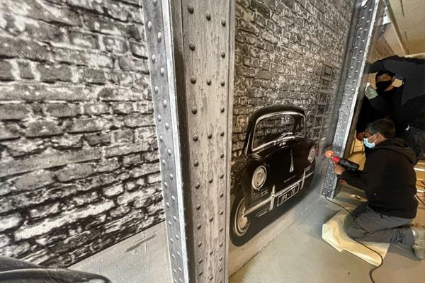 Detalles del vinilo con coches clásicos que cubre la pared del garaje